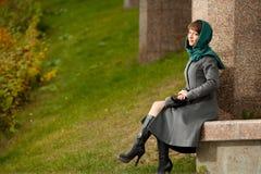 坐灰色的外套的美丽的时髦的妇女户外 库存照片