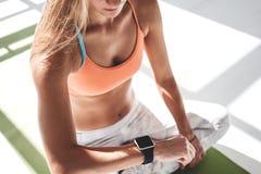 坐瑜伽席子和使用smartwatch的运动的晒斑妇女为检查结果在健身app 库存图片