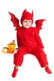 坐用南瓜的红魔服装的小男孩 免版税库存照片