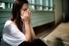 坐用她的手的沮丧的妇女包括她的面孔淹没激动 库存照片