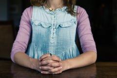 坐用手的妇女foldded在桌上 库存图片
