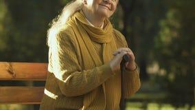 坐用拐棍的愉快的老妇人在公园,残疾的社会关心 股票录像