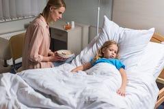 坐用燕麦粥的母亲在病残附近 库存图片