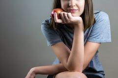 坐用苹果的微笑的女孩在手上 免版税图库摄影