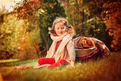 坐用苹果的温暖的围巾的愉快的儿童女孩在秋天庭院里 免版税库存图片