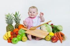 坐用水果和蔬菜的逗人喜爱的婴孩 库存图片