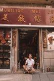 坐由一家商店的年轻人在澳门 库存图片