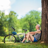 坐由一棵树的资深骑自行车者在公园 免版税库存图片