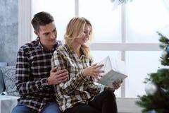 坐由与新年` s装饰和圣诞树的窗口的美好的年轻夫妇 免版税库存图片