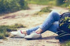 坐由土路的妇女,在蓝色牛仔裤和白色帆布运动鞋,背包由她的边 免版税库存照片
