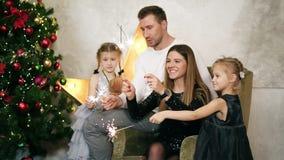 坐由圣诞树和拿着闪烁发光物的幼小愉快的四口之家 逗人喜爱的母亲、父亲和两个女儿 股票视频