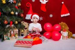 坐由圣诞树的迷人的婴孩 图库摄影