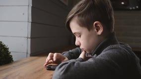 坐由在一个咖啡馆的窗口的青少年的男孩与一个智能手机在他的手上 在人脉的通信 在的比赛 股票视频