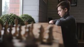 坐由在一个咖啡馆的窗口的青少年的男孩与一个智能手机在他的手上 在人脉的通信 在的比赛 影视素材