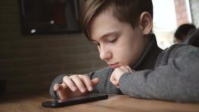 坐由在一个咖啡馆的窗口的青少年的男孩与一个智能手机在他的手上 在人脉的通信 在的比赛 股票录像