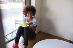 坐由在咖啡馆的窗口的年轻黑人妇女使用智能手机 免版税库存图片