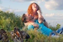 坐由在草和拥抱的篝火的愉快的年轻夫妇 夫妇爱手表 库存照片