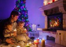坐由壁炉的两个小兄弟姐妹男孩和他们的爸爸  免版税库存图片