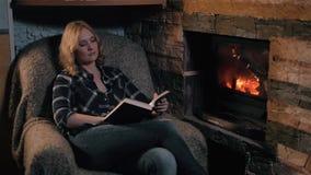 坐由壁炉的美丽的少妇阅读书在乡间别墅里 假日和生活方式概念 股票视频