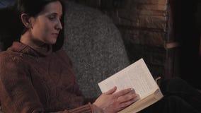 坐由壁炉的美丽的少妇阅读书在乡间别墅里 关闭射击、假日和生活方式概念 股票录像