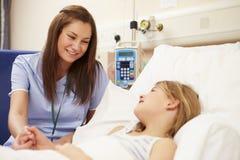 坐由女孩的床的护士在医院 库存照片