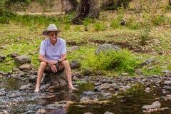 坐由小河的年长澳大利亚人 库存图片