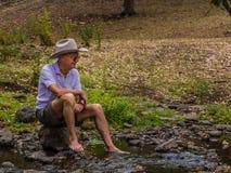坐由小河的年长澳大利亚人 库存照片