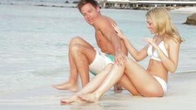 坐由岸的浪漫夫妇在海滩 库存图片