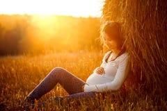 坐由干草堆的年轻人孕妇 免版税库存图片
