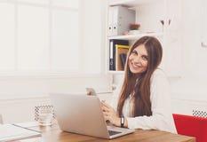 坐由有膝上型计算机的办公桌的美丽的年轻女实业家 库存照片