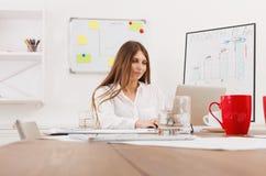 坐由有膝上型计算机的办公桌的美丽的年轻女实业家 免版税库存照片
