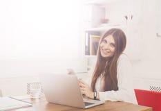 坐由有膝上型计算机的办公桌的美丽的年轻女实业家 免版税库存图片
