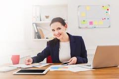 坐由有膝上型计算机的办公桌的美丽的年轻女实业家 免版税图库摄影