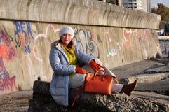 坐由有街道画的墙壁的秋天衣裳的女孩 库存图片