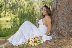 坐由树的愉快的年轻新娘 免版税库存图片