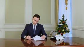 坐由桌的商人读书和签署的文件在办公室在新年树附近 影视素材