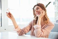 坐由桌的女衬衫的愉快的blondy妇女 库存照片