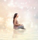 坐由水的愉快的少妇 免版税图库摄影