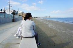 坐由海岸的妇女 免版税库存照片