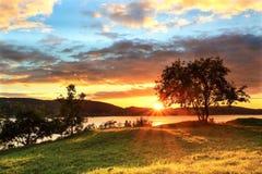 坐由海湾的夫妇在五颜六色的日落在卑尔根 库存图片