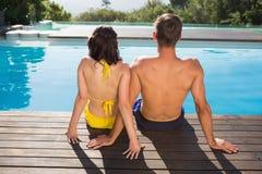 坐由游泳池的夫妇背面图  免版税图库摄影