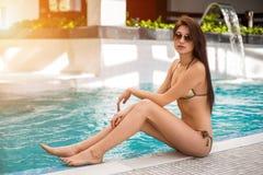坐由游泳池的比基尼泳装的妇女 免版税库存图片