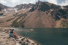 坐由湖的年轻人在优胜美地国家公园 免版税库存照片