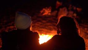 坐由火的年轻夫妇 野营与由海的帐篷 两录影序列  由手扶的后面看法 股票视频