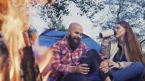 坐由火的愉快的年轻夫妇在帐篷镇 旅客有与一个杯子的休息热的茶在森林在a附近 股票录像