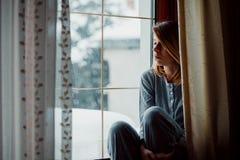 坐由窗口的哀伤的妇女看起来外部 库存图片