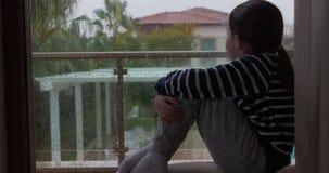 坐由窗口的女孩在下雨天 影视素材