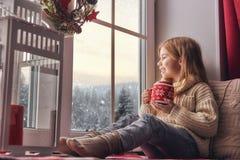 坐由窗口的女孩 库存图片