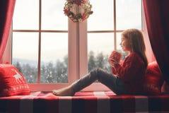 坐由窗口的女孩 库存照片