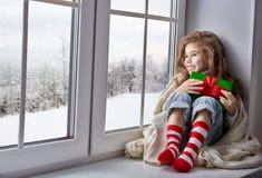 坐由窗口的小女孩 库存图片